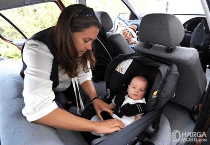 Gambar ini menunjukkan seorang wanita sedang menempatkan anaknya pada kursi khusus anak