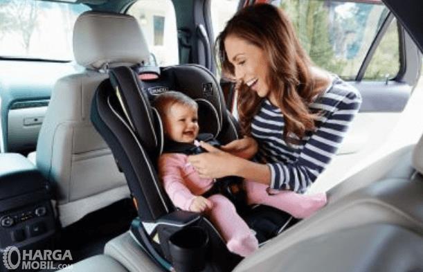 Gambar ini menunjukkan seorang wanita sedang memegang anaknya yang terdapat pada kursi anak
