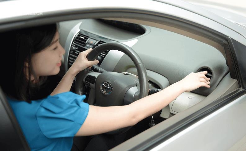 Gambar ini menunjukkan seorang wanita sedang mengatur arah hembusan AC mobil