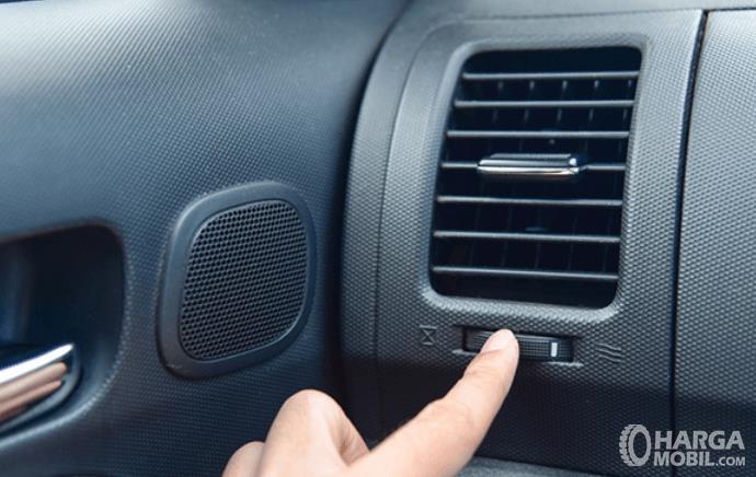 Gambar ini menunjukkan sebuah tangan menekan tombol mengatur arah AC mobil
