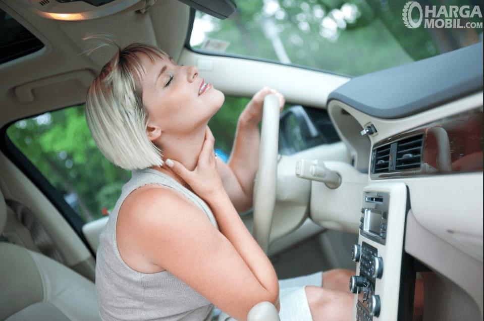 Gambar ini menunjukkan seorang wanita sedang merasakan kesejukan AC di dalam mobil