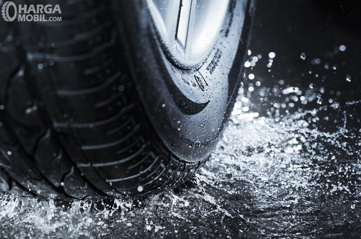 Gambar ini menunjukkan sebuah ban mobil melintasi jalanan yang terdapat air