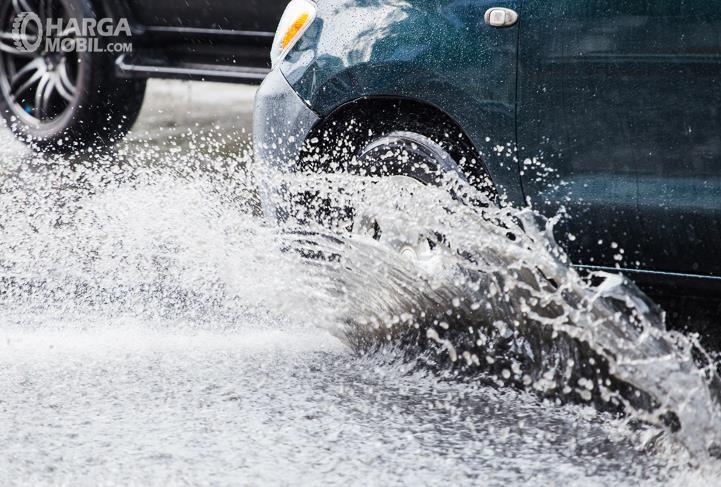 Gambar ini menunjukkan sebuah mobil melewati jalanan yang tergenang air