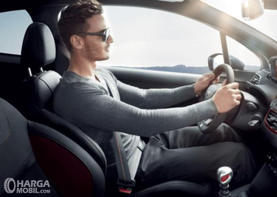 Gambar ini menunjukkan seorang pengemudi pria sedang berada di dalam mobil