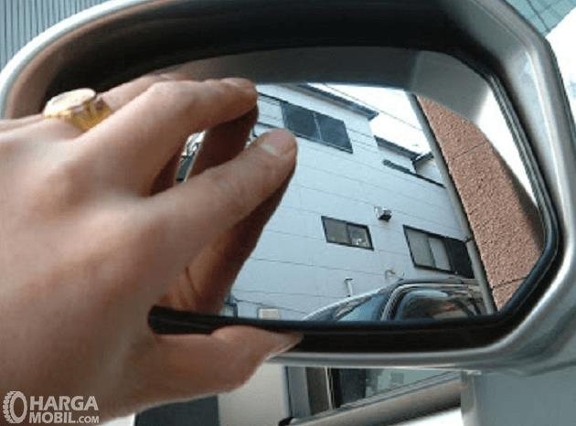 Gambar ini menunjukkan sebuah tangan sedang memegang kaca spion pada mobil