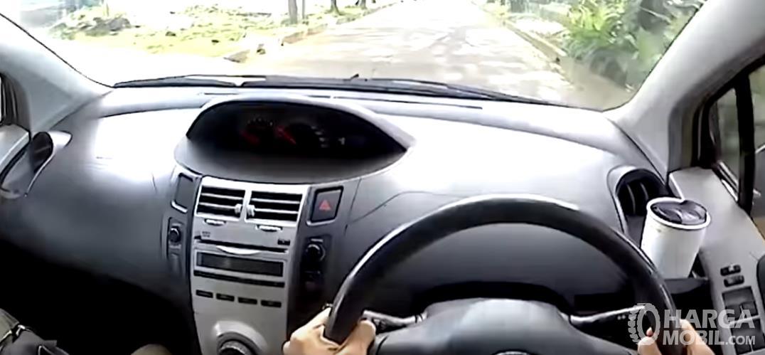 Gambar ini menunjukkan dashboard mobil Toyota Yaris 2006 dan terlihat tangan memegang kemudi