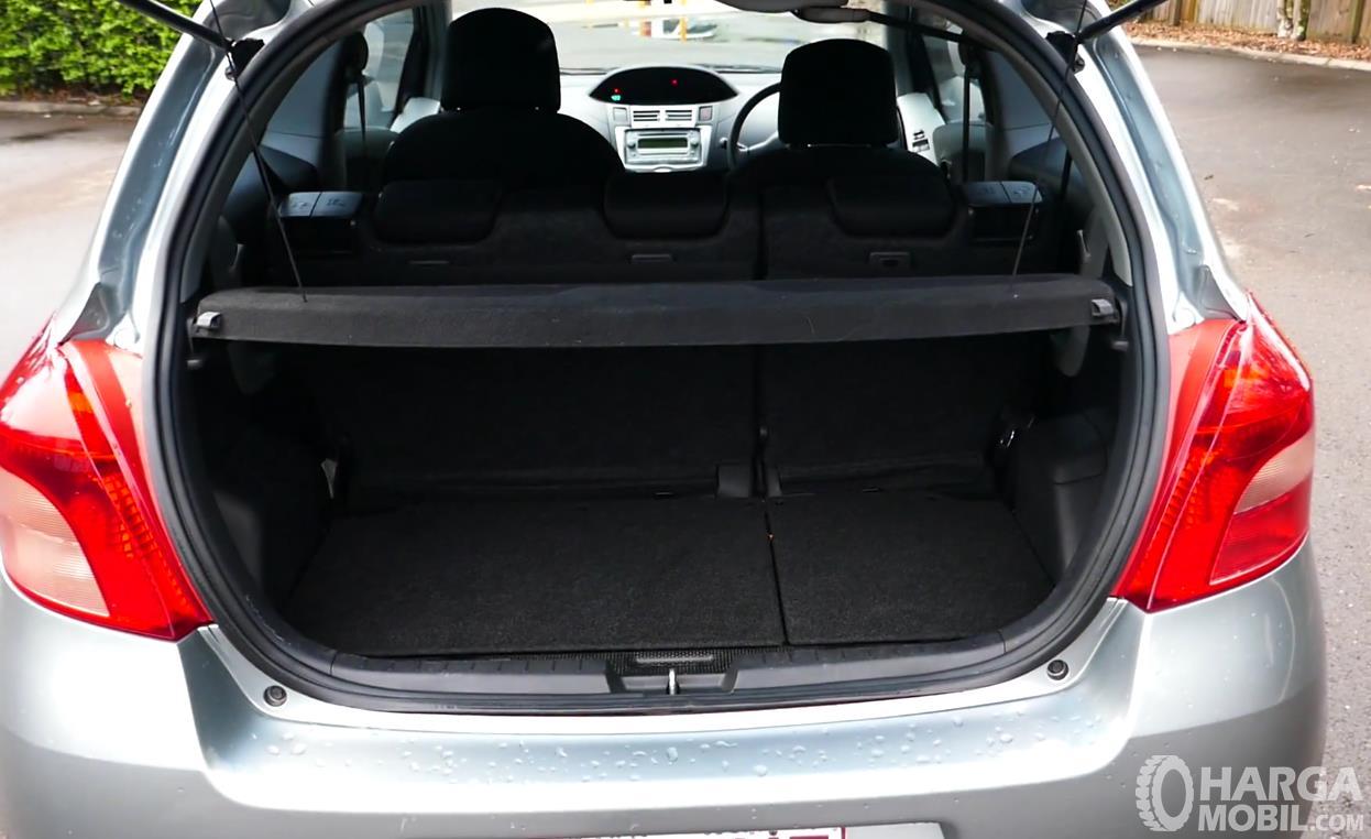 Gambar ini menunjukkan bagasi mobil Toyota Yaris 2006 yang terlihat luas