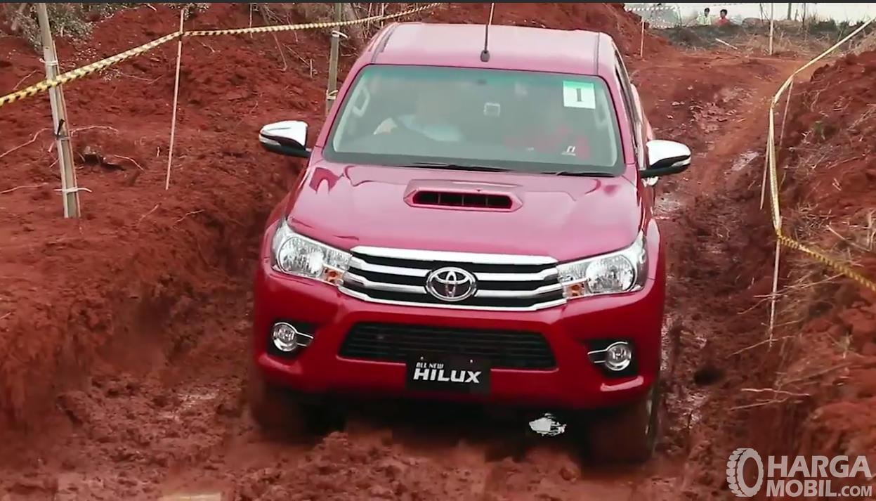 Foto Toyota Hilux berwarna merah sedang di medan off road