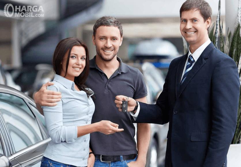 Gambar ini menunjukkan 3 orang 1 wanita 2 orang pria sedang berdiri di di dekat mobil