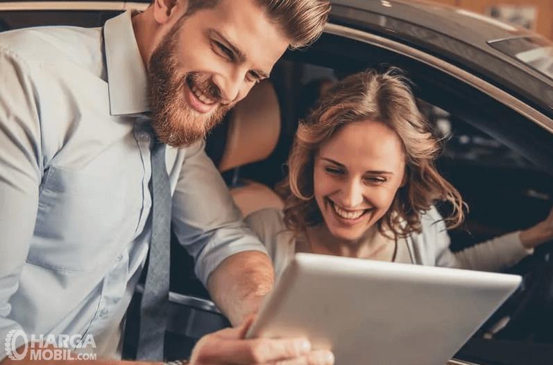 Gambar ini menunjukkan 2 orang sedang melihat ponsel sambil tertawa