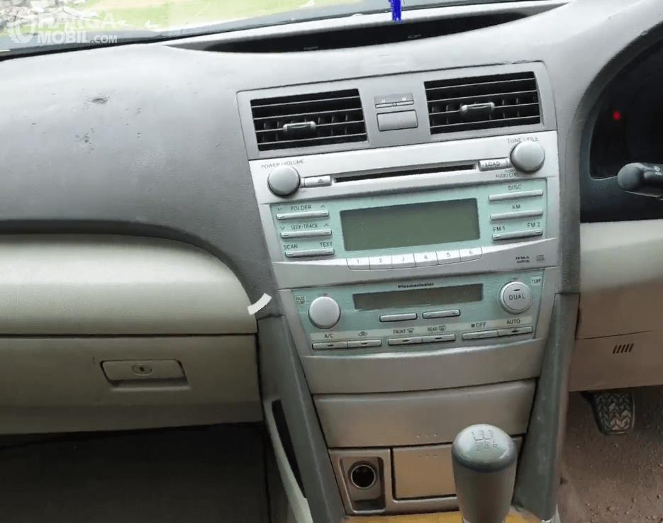 Gambar ini menunjukkan head unit Toyota Camry 2006 dan terlihat beberapa tombol pengaturan