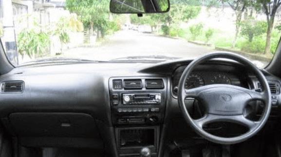 Gambar ini menunjukkan bagian dashboard dan kemudi mobil Toyota Great Corolla 1992