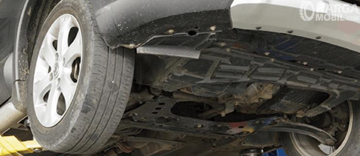 Gambar ini menunjukkan bagian bawah kendaraan dan terlihat beberapa komponen di dalamnya