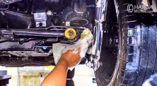 Gambar ini menunjukkan sebuah tangan sedang mencuci kolong mobil