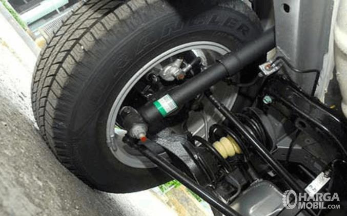 Gambar ini menunjukkan bagian bawah kendaraan dan terlihat suspensi, roda dan bagian lainnya