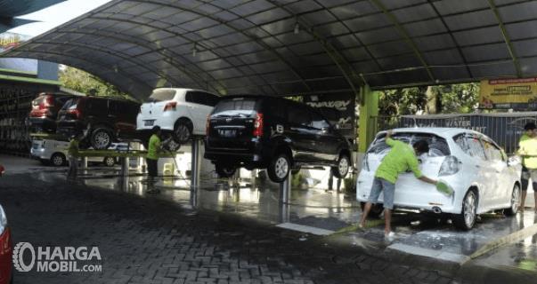 Gambar ini menunjukkan banyak mobil sedang dicuci di salon mobil