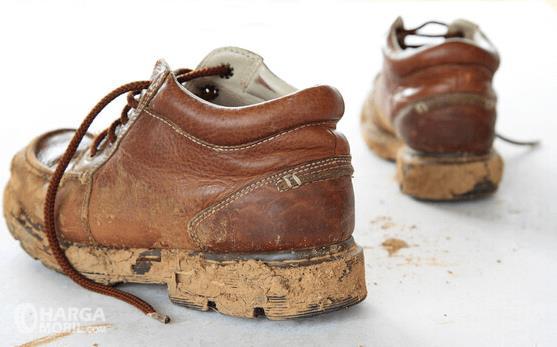 Gambar ini menunjukkan sepasang sepatu warna cokelat dalam kondisi kotor