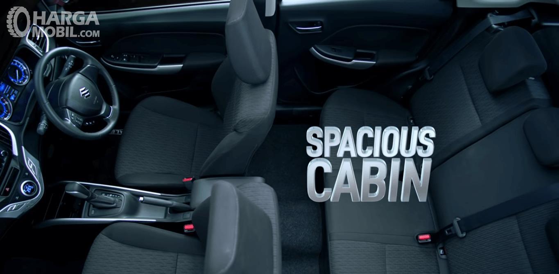 Gambar ini menunjukkan kabin Suzuki Baleno dan terlihat jok dan kemudi mobil