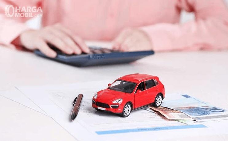 Gambar ini menunjukkan miniatur mobil di atas uang