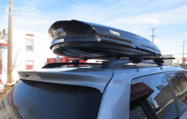 Gambar ini menunjukkan roof box yang ditempatkan di atas mobil