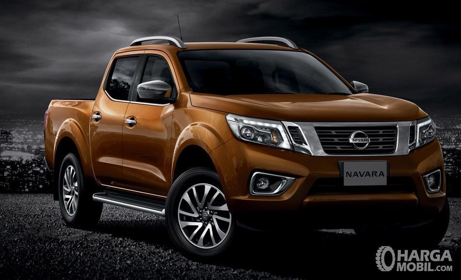 Gambar ini menunjukkan mobil Nissan Navara warna oranye tampak depan