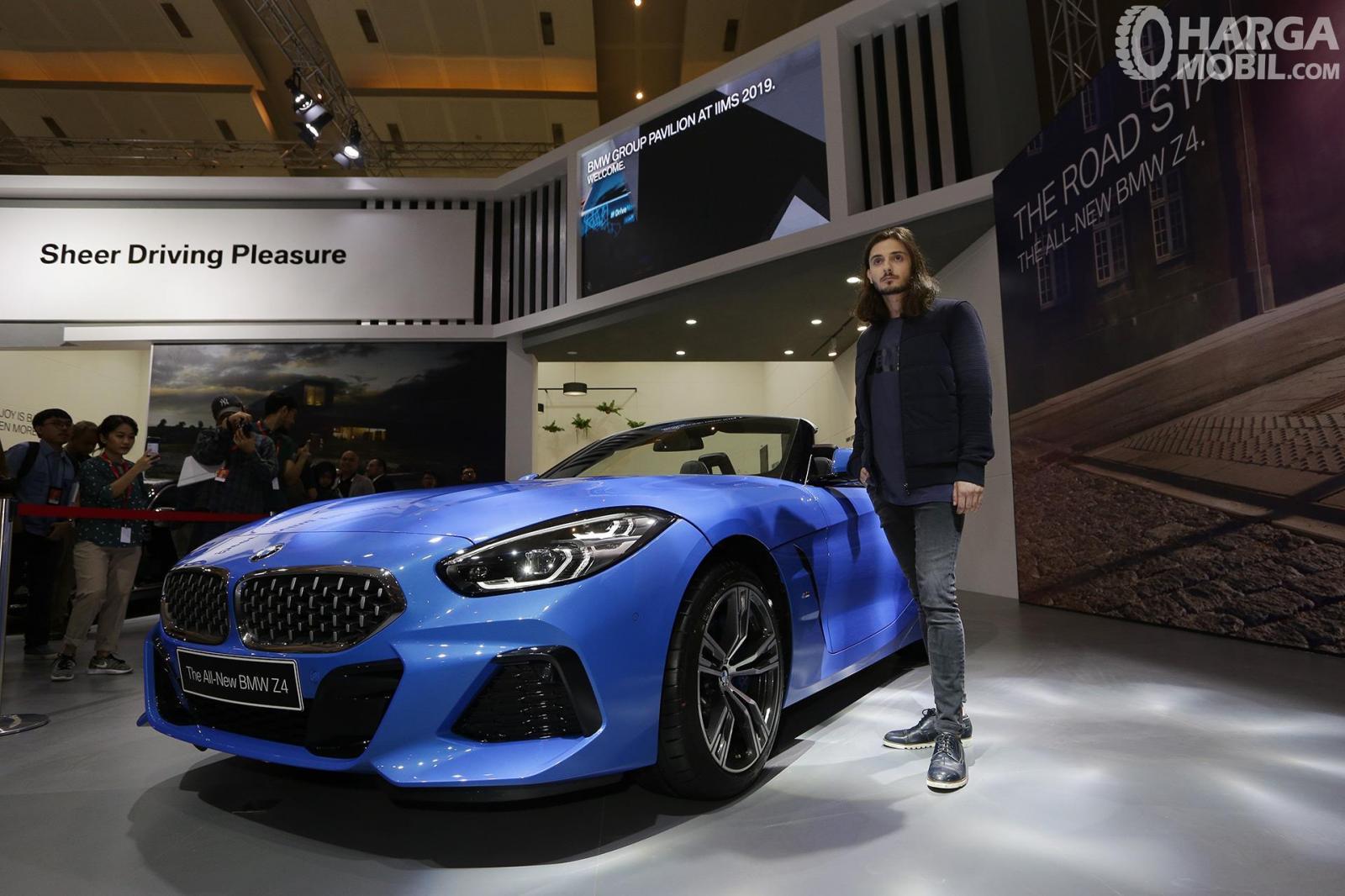 Gambar menunjukkan seorang laki-laki sedang memfoto bersama mobil All New BMW Z4 Hargamobil