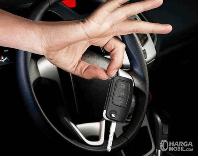 Gambar ini menunjukkan sebuah tangan memegang kunci immobilizer dekat kemudi mobil