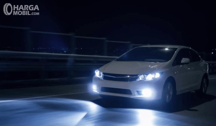 Gambar ini menunjukkan mobil putih sedang melaju di jalan sendirian