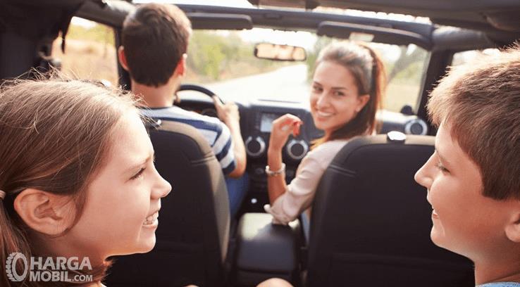 Gambar ini menunjukkan sekeluarga berada di dalam kendaraan