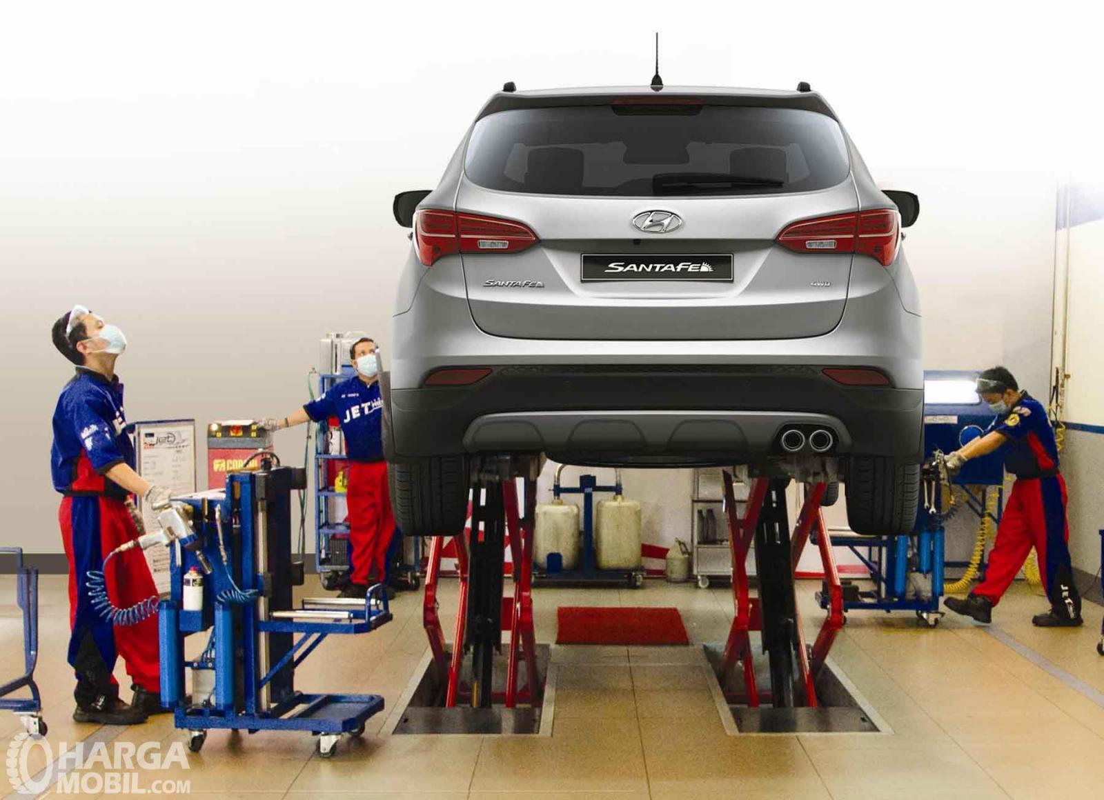 Foto Hyundai Santa Fe sedang diservis para mekanik