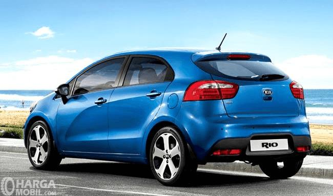 Gambar ini menunjukkan mobil KIA Rio tampak belakang warna biru