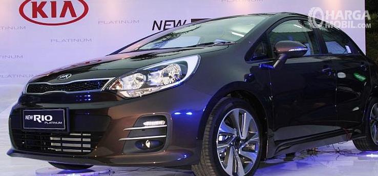 Gambar ini menunjukkan mobil KIA Rio Platinum tampak depan dan samping kiri