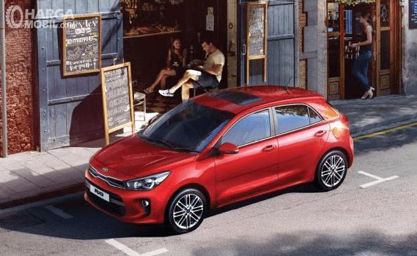Gambar ini menunjukkan mobil KIA Rio Sunroof warna merah tampak samping atas