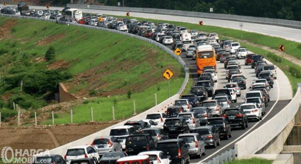 Gambar ini menunjukkan banyak mobil terjebak macet di jalan