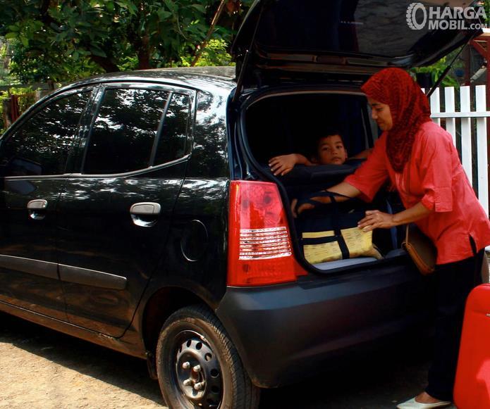 Gambar ini menunjukkan seorang wanita dan anak-anak sedang mempersiapkan perjalanan