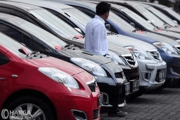 Gambar ini menunjukkan banyak mobil dan terdapat satu orang sedang bediri