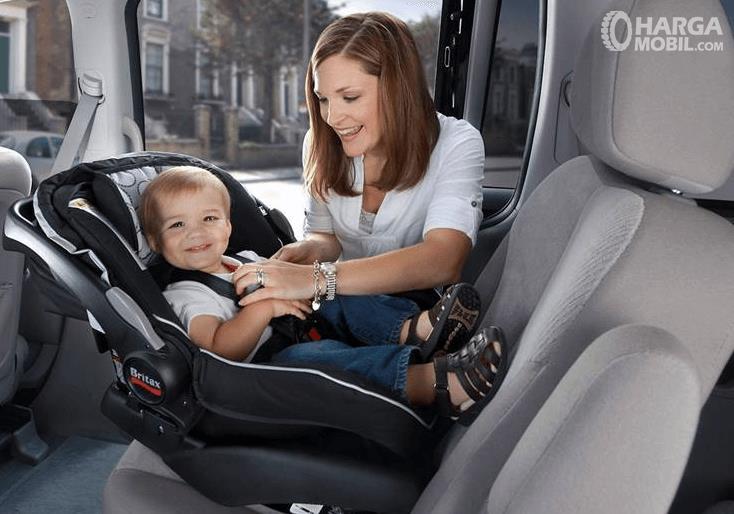 Gambar ini menunjukkan seorang wanita sedang memasang kursi bayi pda mobil