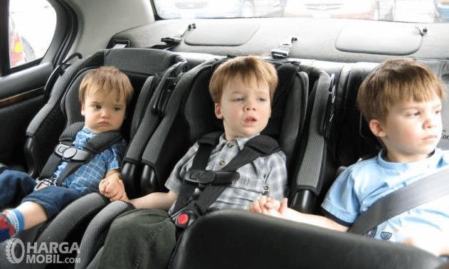 Gambar ini menunjukkan 3 orang anak sedang duduk di kursi baris belakang