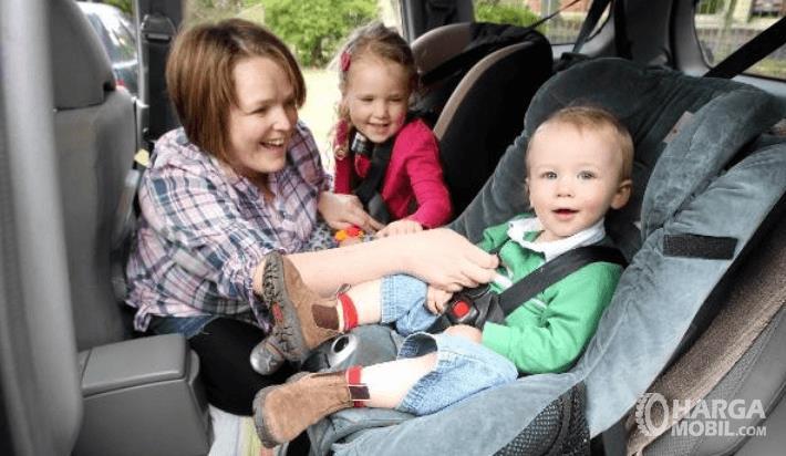 Gambar ini menunjukkan seorang ibu dan 2 anak sedang ditempatkan di kursi mobil