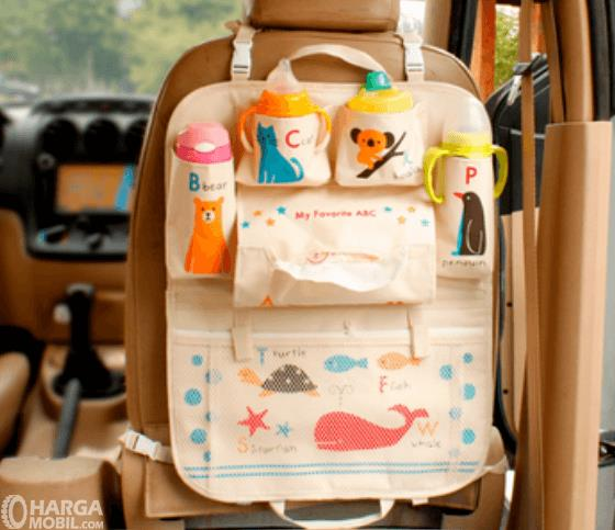 Gambar ini menunjukkan perlengkapan anak diletakkan pada bagian belakang jok mobil