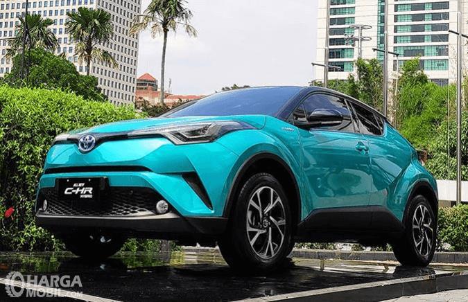 Gambar ini menunjukkan mobil Toyota C-HR Hybrid 2019 warna biru tampak depan dan samping kiri