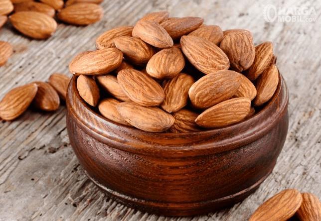 Gambar ini menunjukkan almond yang terdapat pada mangkok warna coklat