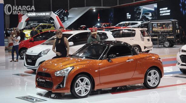 Gambar ini menunjukkan beberapa mobil dan beberapa orang sedang berada di pameran