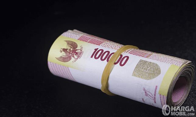 Gambar ini menunjukkan uang 100 ribuan diikat dengan karet