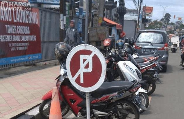Gambar ini menunjukkan rambu dilarang parkir dan beberapa motor dan satu mobil di belakangnya