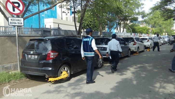 Gambar ini menunjukkan proses penertiban mobil yang parkir sembarangan