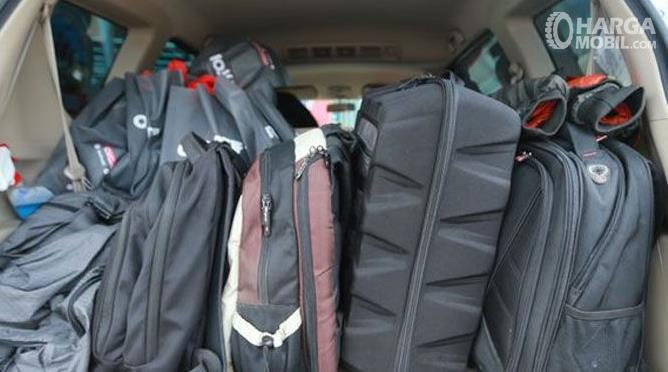 Gambar ini menunjukkan beberapa koper dan tas diletakkan di bagasi mobil