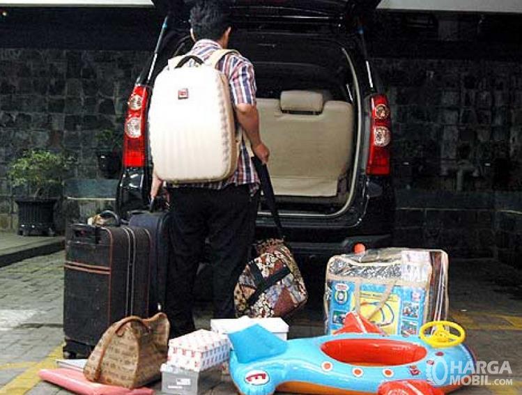 Gambar ini menunjukkan seseorang akan memasukkan barang di bagasi mobil