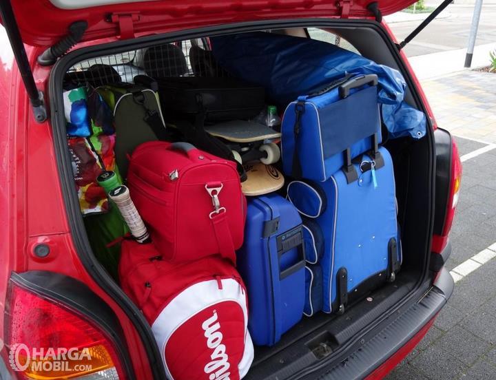 Gambar ini menunjukkan banyak barang ditempatkan di bagasi mobil warna merah