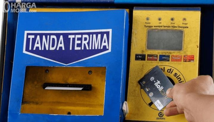 Gambar ini menunjukkan penempelan kartu E-Toll di gerbang Tol